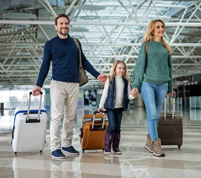 young happy family pulling suitcases through airport