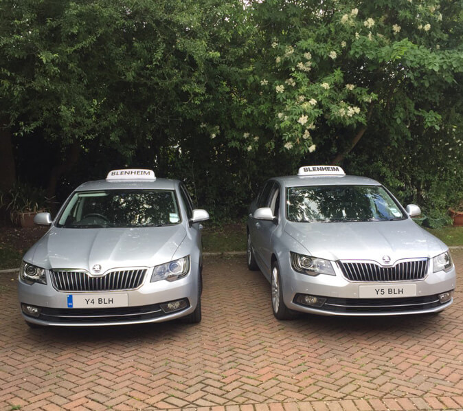two silver skoda saloons blenheim taxis parked side by side