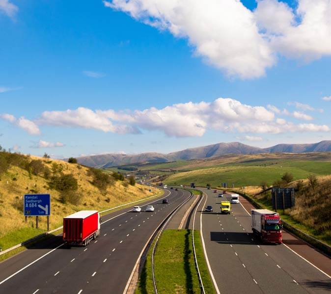 UK motorway traffic with large blue sky and farm land